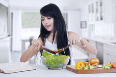 Young woman cooks salad at home Royalty Free Stock Photo