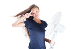 Young woman cooling herself under wind of cooler fan isolated on white background Stock Image