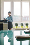 Young woman copying document with photocopy in office. Female secretary working in office, copying document and paperwork with copy machine in modern office royalty free stock photography