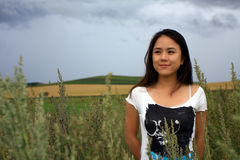 Young Woman in Cornfield. Young woman standing in cornfield with a sweet smile Royalty Free Stock Photography