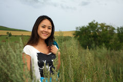 Young Woman in Cornfield. Young woman standing in cornfield with a sweet smile Royalty Free Stock Images