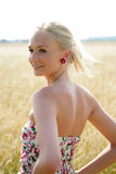 Young woman in a cornfield. Young blonde woman stands in a cornfield wearing a summer dress. She looks over her left shoulder and smiles into the camera Royalty Free Stock Images