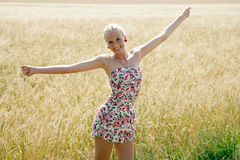 Young woman in a cornfield. Young blonde woman in a summer dress is standing in front of a cornfield Stock Image