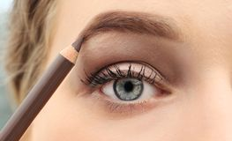 Young woman correcting shape of eyebrow with pencil. Close up Stock Photography