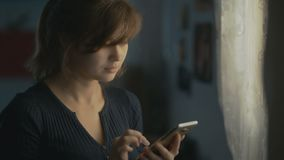 A young woman is corresponding in the phone at home, the girl is having fun on the Internet, but is distracted by a person nearby