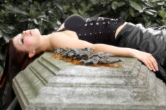 Young woman with corset laying. On a grave stock photo