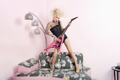 Young woman in corset playing guitar while standing on furniture Stock Photo