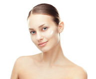 Young woman with cosmetic cream on a cheek Royalty Free Stock Images