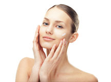 Young woman with cosmetic cream on a cheek Royalty Free Stock Photos