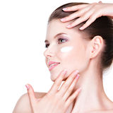 Young woman with cosmetic cream on a face. Stock Images