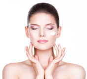 Young woman with cosmetic cream on a face. Stock Photos