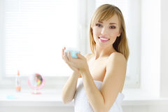 Young woman with cosmetic cream Stock Images