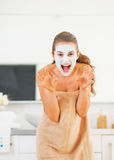 Young woman with cosmetic mask on face scaring. In bathroom Stock Photo