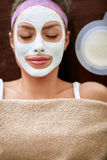 Young woman with cosmetic mask on her face Stock Image