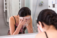 Young woman with cosmetic mask spraying water on her face standi Stock Images