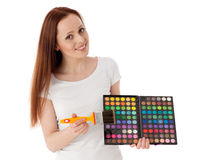 Young woman with cosmetic palette and paintbrush. Stock Photography