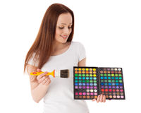 Young woman with cosmetic palette and paintbrush. Stock Photo