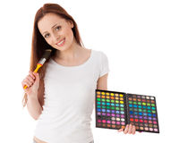 Young woman with cosmetic palette and paintbrush. Stock Image