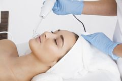 A young woman during a cosmetic procedure. The profile of a woman who lies in the beautician during the procedure. Meanwhile, the cosmetician makes the surgery Stock Photos