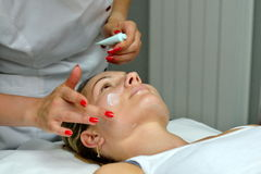 Young woman during cosmetic treatment Stock Images