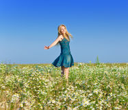 The young woman costs in the field having parted hands in the parties Stock Photo