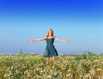 The young woman costs in the field with wild flowers having parted hands in the parties Stock Images