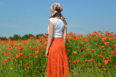 The young woman costs in a poppy field Stock Images