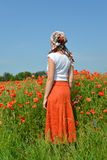 The young woman costs in a poppy field Royalty Free Stock Images