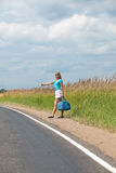 The young woman costs on a road roadside Royalty Free Stock Photos
