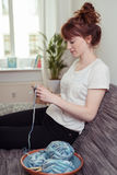 Young Woman at the Couch Crocheting with Yarn Stock Image