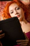 Young woman on a couch with tablet pc Royalty Free Stock Images