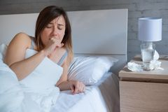 Sick woman coughing while lying in bed stock photos
