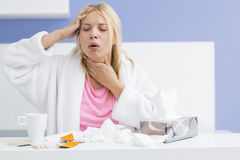 Young woman coughing while suffering from headache and cold in kitchen. Young women coughing while suffering from headache and cold in kitchen Stock Images