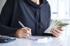 Young woman counting money with calculator Royalty Free Stock Images
