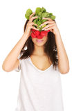 Young woman cover with bunch of radishes. Stock Photos