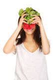 Young woman cover with bunch of radishes. Royalty Free Stock Photography
