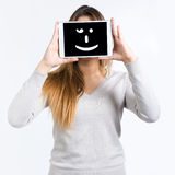 Young woman cover her face with digital tablet. Isolated on whit Stock Photo