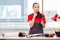 The young woman in coveralls doing repairs. Young woman in coveralls doing repairs Stock Photo