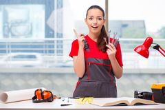 The young woman in coveralls doing repairs Stock Photo