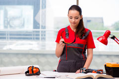 The young woman in coveralls doing repairs Royalty Free Stock Images
