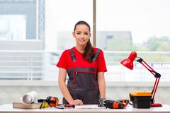 The young woman in coveralls doing repairs Stock Images