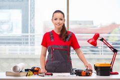 The young woman in coveralls doing repairs Stock Image