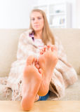 Young woman covered with blanket. Sitting on the sofa at home. Focus on feet Royalty Free Stock Photography