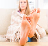 Young woman covered with blanket. Sitting on the sofa at home. Focus on feet Stock Photo