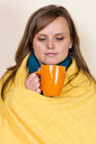 Young woman covered with a blanket, holding a cup of tea, sittin Stock Images