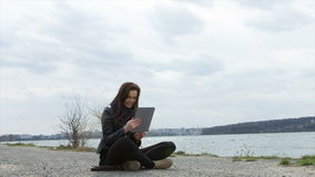 Young woman covered with blanket using tablet PC. At the beach stock footage