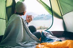 Young woman covered with warm plaid meets cold morning in sitting in a touristic camping tent with a cup of hot tea. Romantic cam stock photos