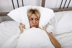 Young woman covering ears with pillow in bed Royalty Free Stock Images