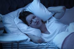 Young woman covering ears with pillow while trying to sleep in bed. At night royalty free stock photography