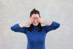 Young woman covering eyes with hands. Young woman covering eyes with both hands in front of grey wall Royalty Free Stock Photos